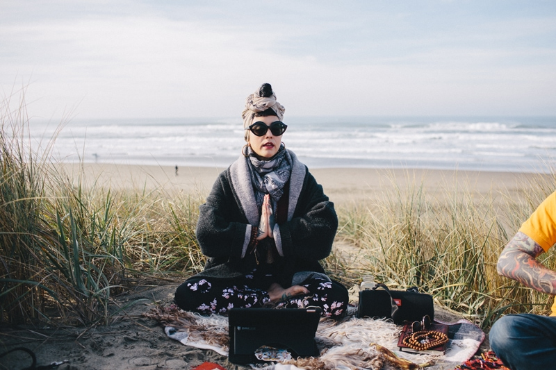 Psychedelic Counseling, Woman sitting next to ocean with her legs crossed
